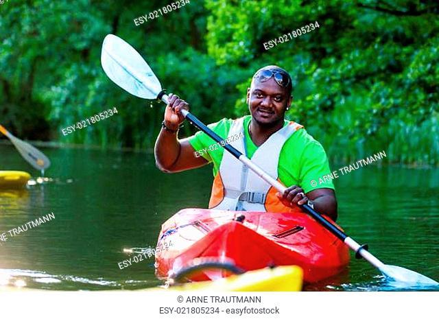 Afrikanischer Mann fährt im Kajak auf Wald Fluss