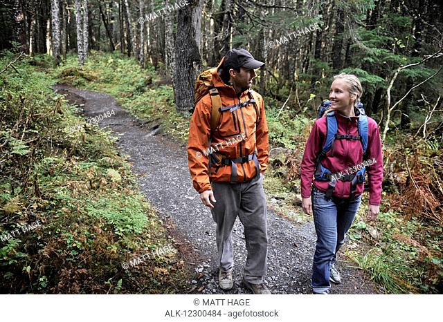 Backpacking couple walks a forested trail in the Chugach National Forest of Southcentral Alaska