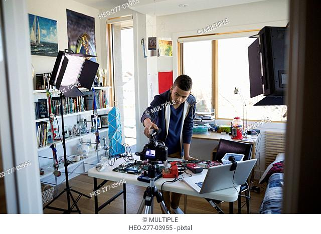 Boy videotaping circuit board assembly in bedroom