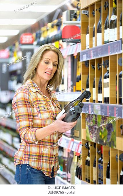 Woman Choosing Wine In Supermarket