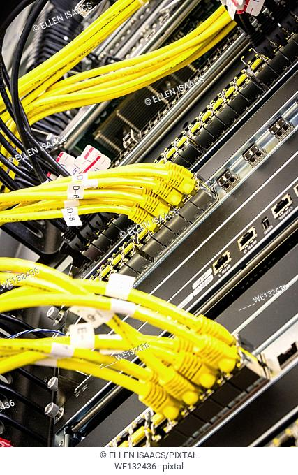 Yellow ethernet cables plugged into a high end router machine at a computer data center