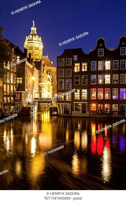 Illuminated buildings by canal at night