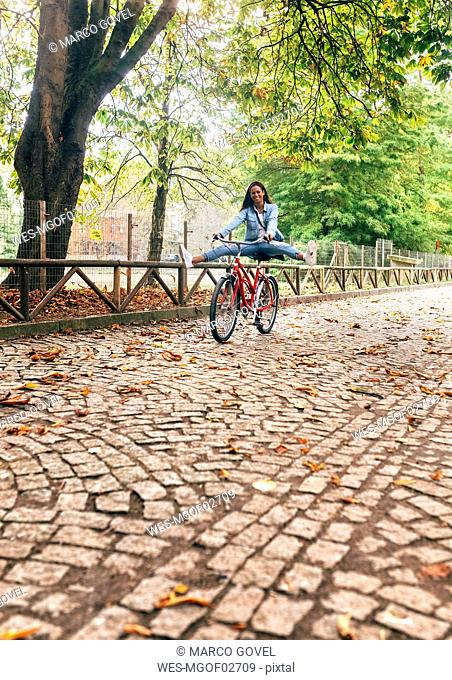 Happy young woman riding a bike in a park