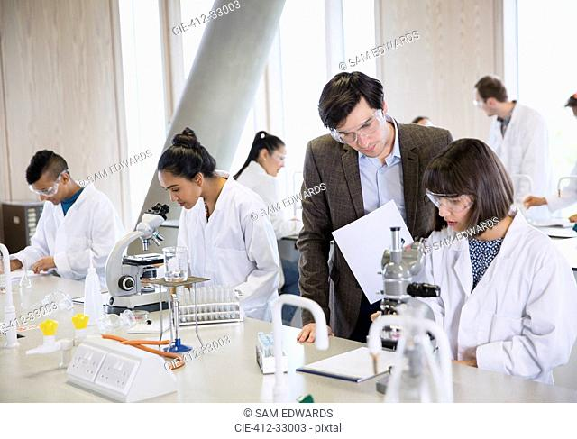 Science professor helping college student conducting scientific experiment in science laboratory classroom