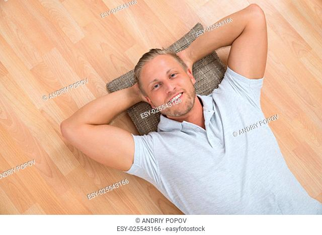 Young Happy Man Lying On Floor With Cushion