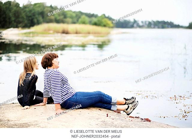 Mother with daughter relaxing at lake