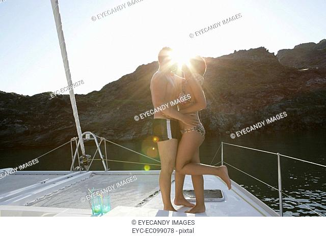 Young couple kissing on a boat, sunburst between faces