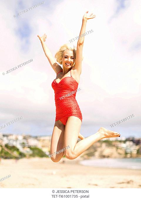 Woman wearing red one piece swimsuit jumping on sandy beach
