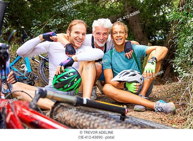 Portrait happy male friends mountain biking, resting