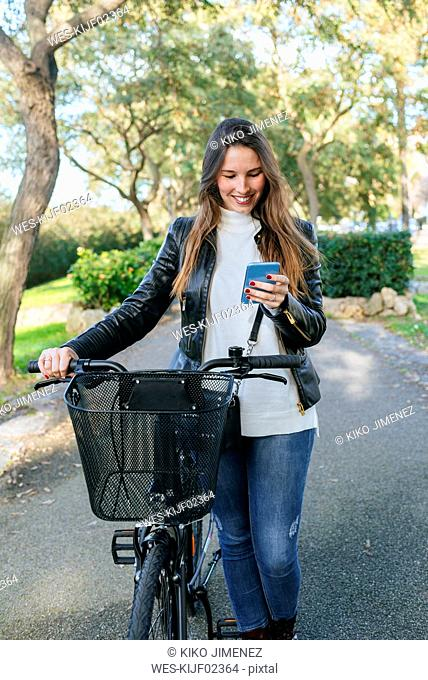 Smiling young woman with bicycle in park using cell phone