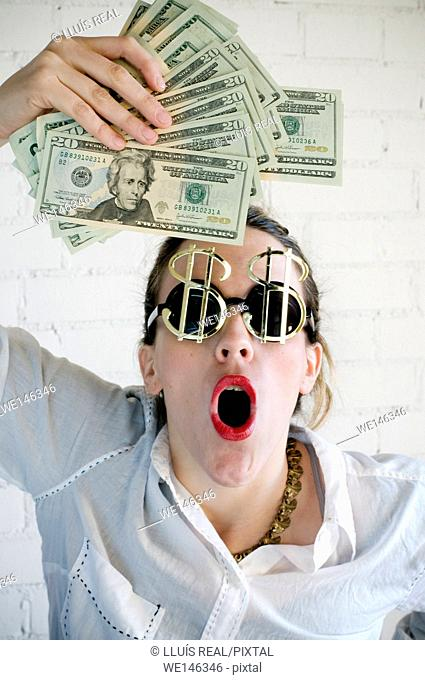 Young woman with sunglasses with a symbol of the dollar and lots of dollars in hands with a surprise expression