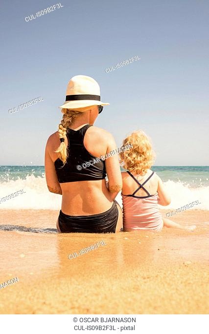 Rear view of woman and daughter sitting on beach at waters edge, Altea, Alicante Province, Spain