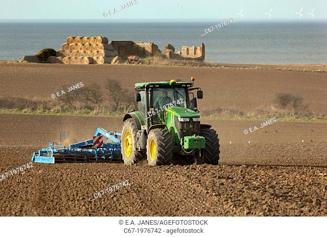 Seed drilling at Cley Norfolk in Spring and off shore windfarm