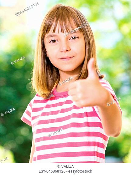Portrait of happy girl 10-11 year old showing thumb up gesture. Beautiful schoolgirl posing outdoors