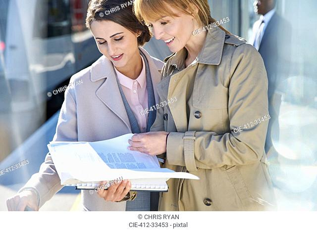 Businesswomen reading paperwork on sunny train station platform