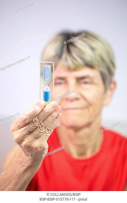 Old woman looking at an hourglass