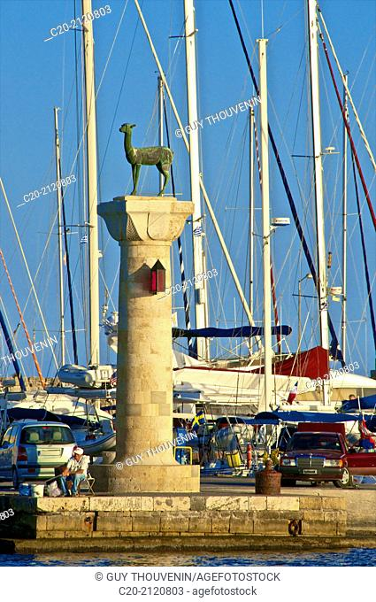 doe bronze statues, symbol of Rhodes, at the entrance of Mandraki harbor, with boats, Rhodes island, Greece