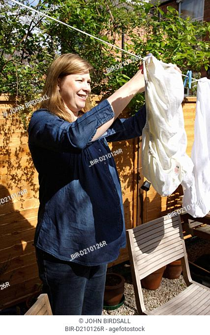Pregnant woman hanging out washing