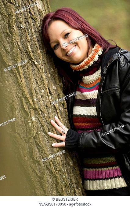 woman leans on a tree