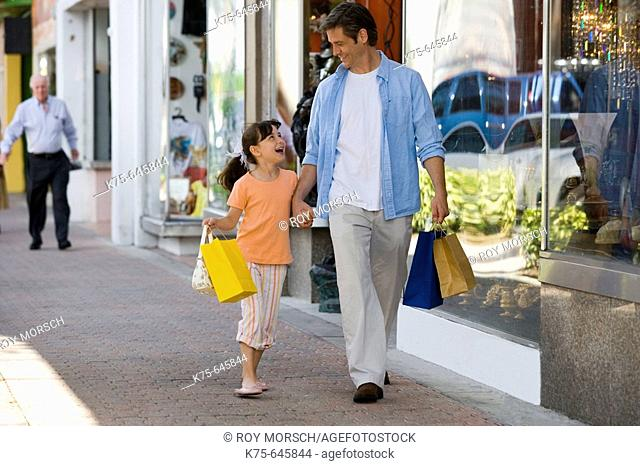 caucasians, dad, age 30 to 40, daughter, age 9, shopping, laughing, walking, hand in hand, happy