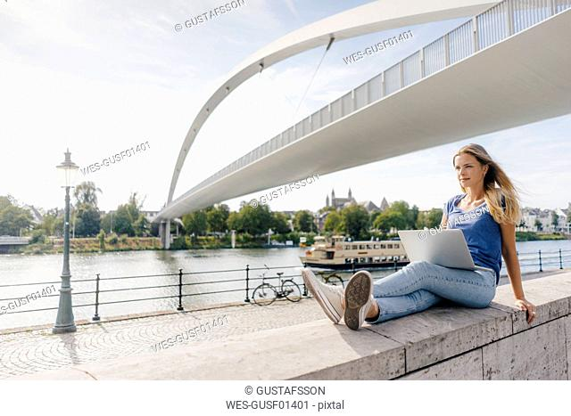 Netherlands, Maastricht, young woman sitting on a wall at the riverside with laptop