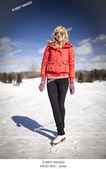 Caucasian woman on ice skates on frozen lake