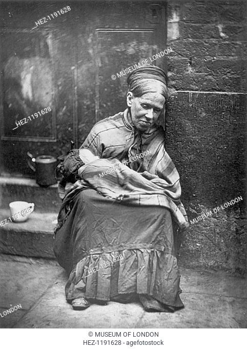 'The crawlers', 1877. A poor woman sits in a doorway holding a baby in her arms