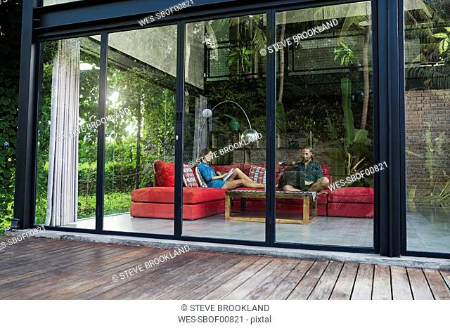 Garden view through glass facade of couple with laptop and book relaxing on red couch in modern design house
