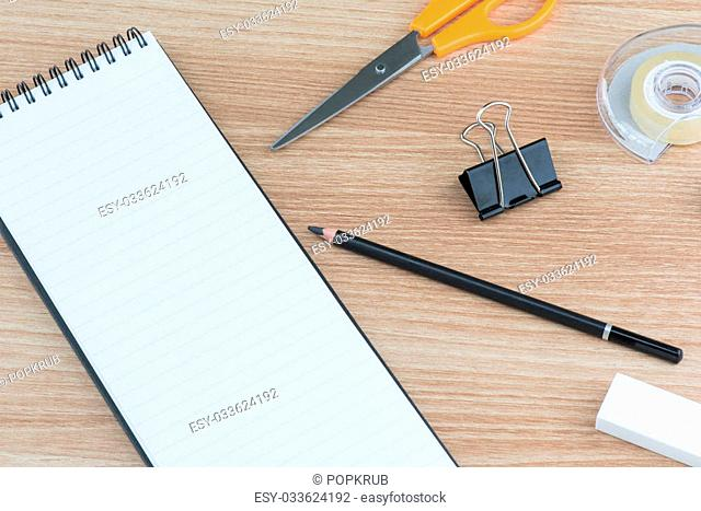 Opened blank ring spiral binding lined notebook with stationary on wooden surface, writing concept, your own contents, space for text
