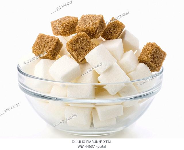 Lumps of brown sugar in glass bowl on white