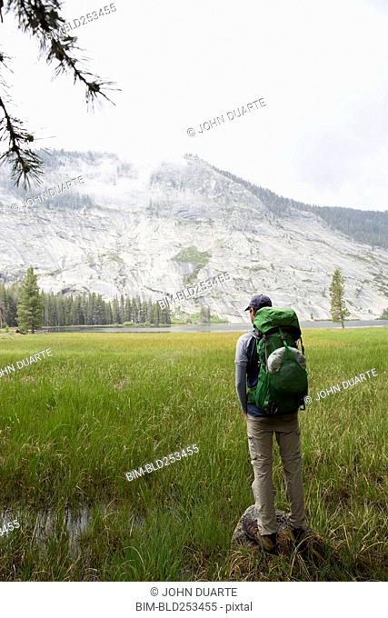 Caucasian man backpacking near mountain