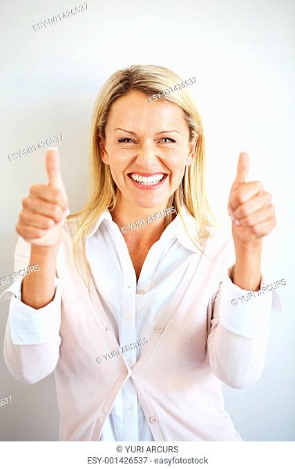 Portrait of a happy young female showing goodluck sign against grey background