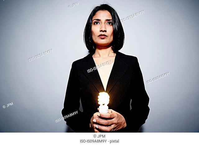 Studio portrait of businesswoman holding energy saving lightbulb