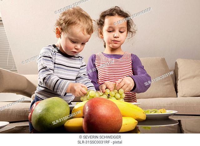 Boy and girl eating fruit
