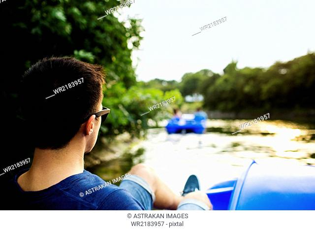 Rear view of man pedaling boat on river against sky