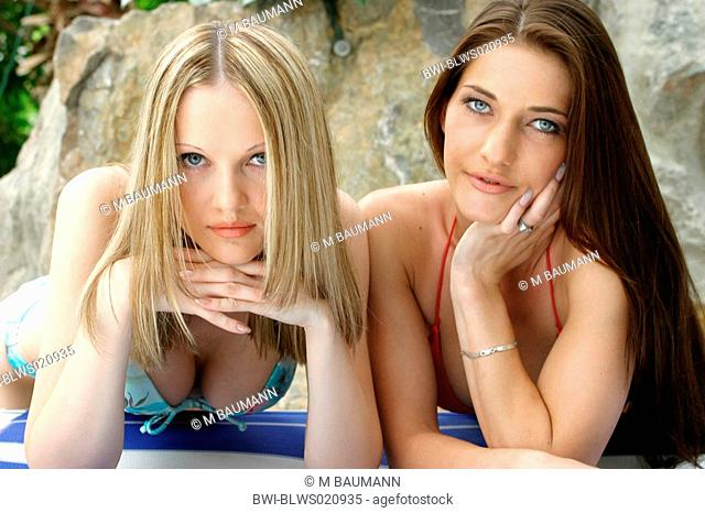blond and brunette woman lying side by side