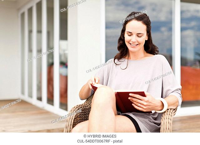 Woman reading book in backyard