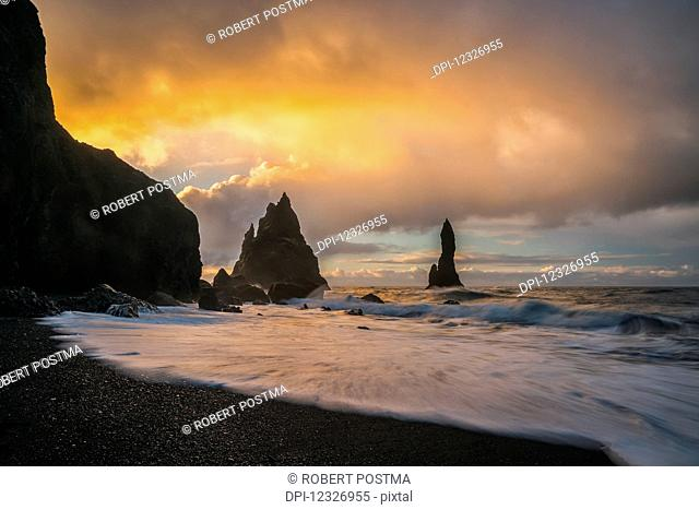 The sea stacks known as Reynisdrangar with waves at sunrise, South Coast; Iceland