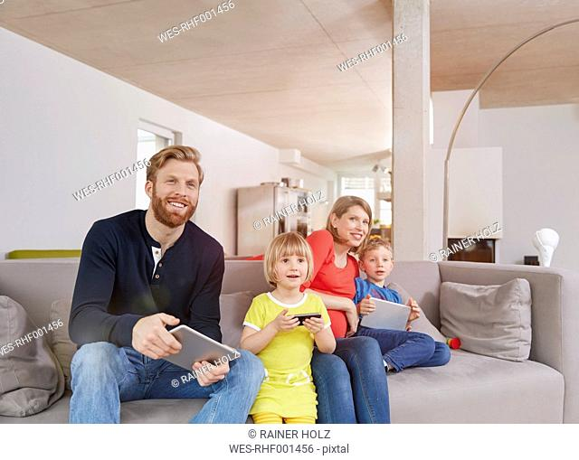 Family of four with mobile devices on couch