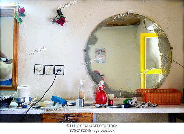 Closeup of a barbershop dresser with a mirror, sockets and flowers on the wall, bottles, barber brush and utensils in Morocco, Africa