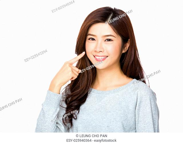 Young woman finger point to her teeth
