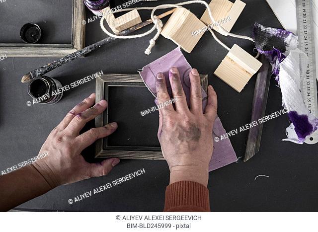Hands of Caucasian artist sanding picture frame