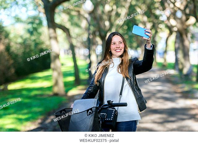 Smiling young woman with bicycle in park taking a selfie