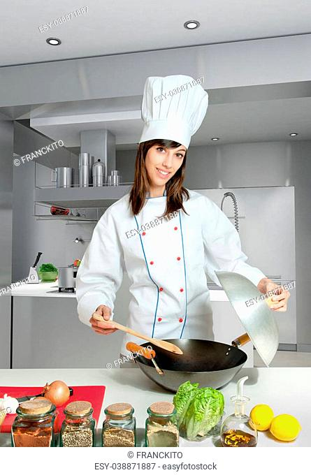 Young female chef with a wok in a kitchen interior