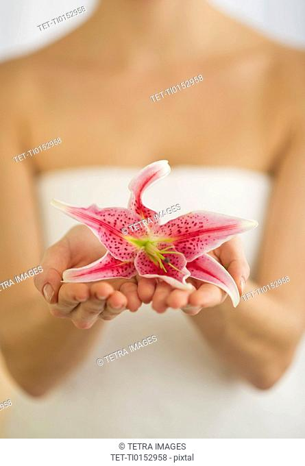 Studio shot of woman holding lily