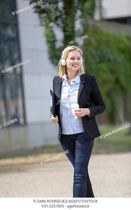 Pretty executive woman walking with coffee and headphones outdoors