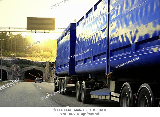 Blue heavy transport truck drives on motorway among traffic towards a road tunnel and evening sunset