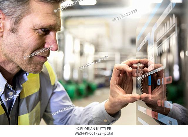 Man using touchscreen device in industrial plant