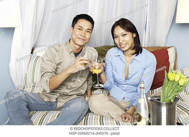 Portrait of a young couple sitting on the bed toasting with wineglasses