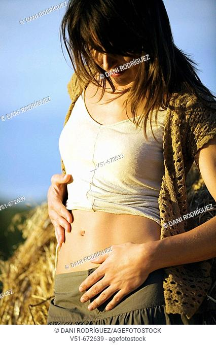 Woman looking at her belly in the countryside